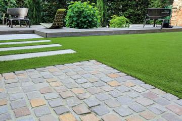 Moderne Garten- und Terrassengestaltung: Materialmix aus Pflastersteinen, Betonsteinen, Holz und Kunstrasen