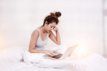 The lady is using laptop for work,very sleepy,in bedroom,blurry light around.