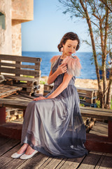 a young nymphet sits in a dress on a bench with the sea on the background and pulls the feathers on her dress