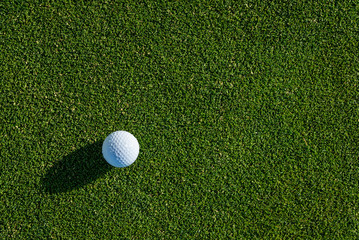 Early morning on the golf green, still covered in dew and sparkles from the sun, side light on a golf ball and a big shadow
