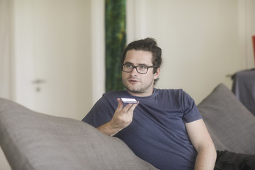 Man sitting in living room talking on mobile phone