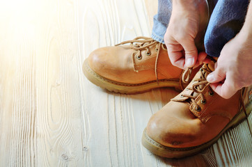 Carpenter in blue jeans tying shoelaces of yellow work boots on on wooden floor. Place for text
