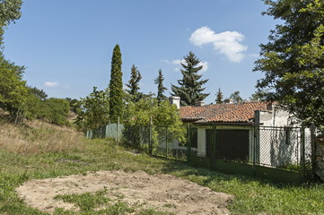 Part of street in the Paunovo village with old house, tree and fence, Sredna Gora mountain, Ihtiman, Bulgaria, Europe