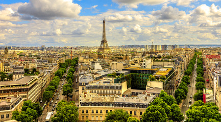 Arch of Triumph panorama from Place Charles de Gaulle square. Trees street Avenues Marceau, d'Iena and Kleber in Paris, France, Europe. Distant view of Tour Eiffel tower in Paris cloudy skyline.