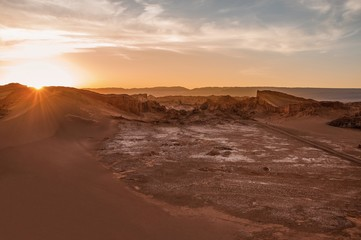 Sun star formed as the sun sets down at the other side of a massive moon crater at Valle de la Luna, or Moon Valley, Atacam desert, northern Chile.