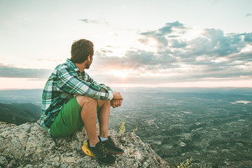 Guy sitting on a rock on the mountain watching a sunset. Social network style photo