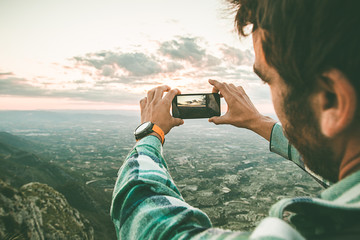 Man taking a photo with his mobile phone to a sunset. Guy taking a picture of a sunset in the mountains