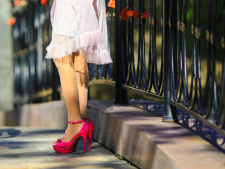 slender women's legs in red high-heeled shoes