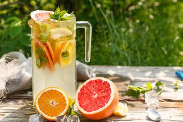 citrus lemonade in glass jug with mint. Orange. Grapefruit and lemon. On greenery background.