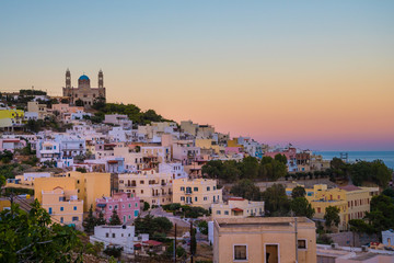 Panoramic view of Ermoupoli city of Syros Island in Cyclades, Greece.  View of the colorful houses and the Orthodox Anastaseos church on sunset