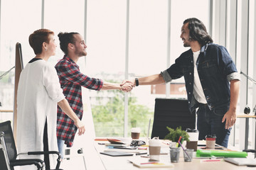 Two businessmen shaking hands in agreement in casual business setting at office