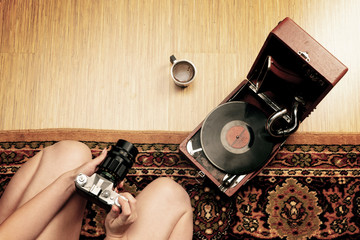 Hipster style. The girl removes the film on the camera gramophone, coffee.