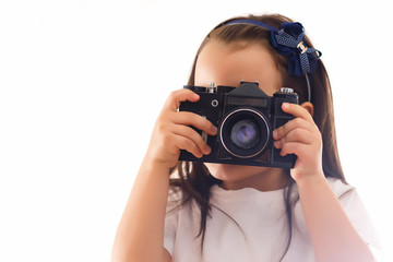 Girl taking a picture with a professional retro camera isolated on white
