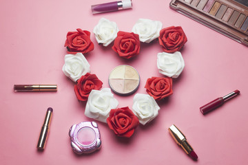 heart shaped from red and white roses flowers and differents colorful lipsticks and face powder and eye shadow