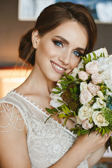 Stylish and sensual young brown-haired model woman with wedding hairstyle and bright makeup, in stylish lace dress with bouquet of flowers in her hands posing at interior