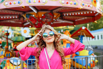 Bright summer concept. A cheerful blonde girl in pink jacket and stylish sunglasses is having fun in the amusement Park. Cheerful woman smiling against bright carousel
