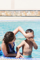 A girl and little boy playing in the swimming pool. Summer vacation concept.