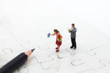 Miniature people: Students read books on the jigsaw board and pencil. Image use for education concept.