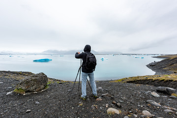 Back of young man photographer in cold winter coat taking pictures photographing blue glacier icebergs in lagoon lake in Iceland on tripod