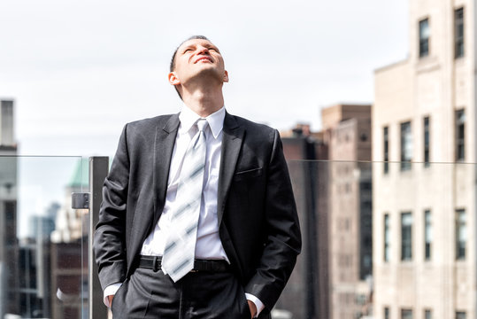 Young businessman standing in business suit looking up at sky in New York City cityscape skyline in midtown Manhattan after interview break at skyscrapers rooftop