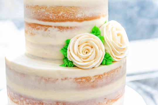 Macro closeup of three tiered vanilla golden light white yellow cream sponge wedding cake with rose flowers decoration on bright stand, artificial color green leaves