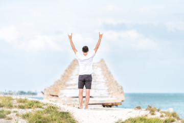 Young man standing in front of Knights Key-Pigeon Key-Moser Channel-Pacet Channel Bridge (Old Seven Mile Bridge) with both arms raised in air