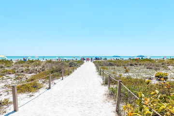 Bowman's beach at Sanibel Island with sandy trail, path, walkway, fence, many people, crowd in distance, crowded coast, coastline shelling, looking for shells