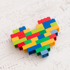 Heat made of colorful plastic toy bricks on white wooden table background.