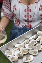 Woman holding a tray of oysters