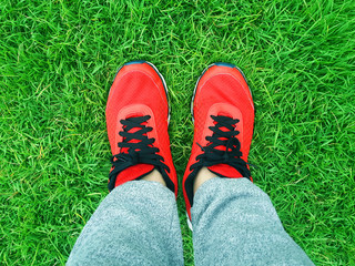 red sneakers on a background of green grass