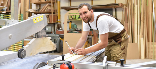 Fototapeta friendly carpenter with ear protectors and working clothes working on a saw in the workshop obraz