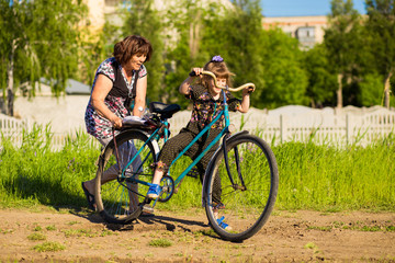 Grandmother teaches little granddaughter to ride old big bike