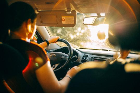 Frau fährt Auto in der Abendsonne