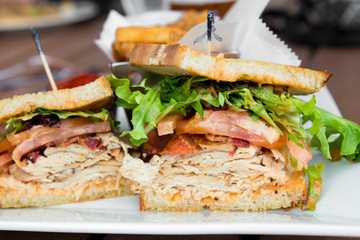 Photo on textile frame Snack Delicious turkey club sandwich on toast with bacon, lettuce and tomato.