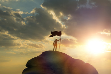 silhouette of a man on top of a mountain holding a flag of victory, against the sky and sunset. Concept business idea. achievements, success, career ladder, work