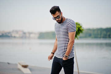 Handsome tall arabian beard man model at stripped shirt posed outdoor. Fashionable arab guy at sunglasses.