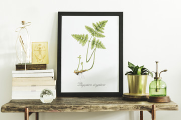 Stylish scandinavian composition of wooden console with mock up poster frame, books, plants, sprinkler and accessories. Modern composition of home interior.