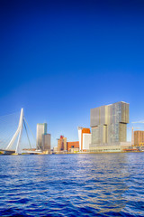 Travel Destinations. Amazing Sunny Cityscape View of Rotterdam Harbour and Port in Front of Erasmusbrug (Swan Bridge) on Background During Daytime.