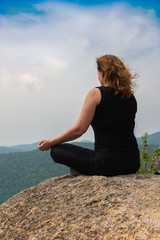 On a mountaintop/ Young female rock climber meditating on top of a mountain