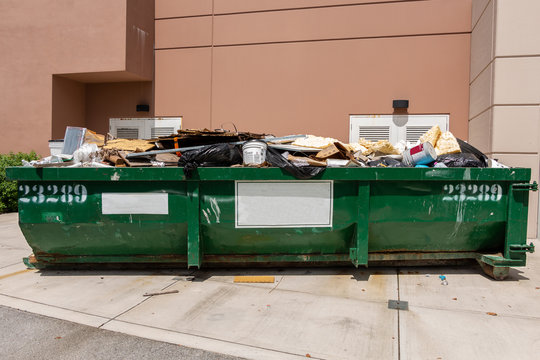 Large green metal dumpster filled with garbage from building renovation - Fort Lauderdale, Florida, USA