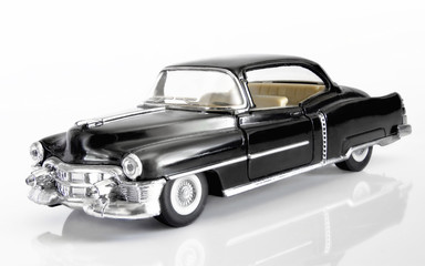 The classical American car of 1952 of release of black color on a white background with reflection.