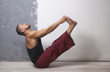 Young strong man practices yoga and gymnastics,