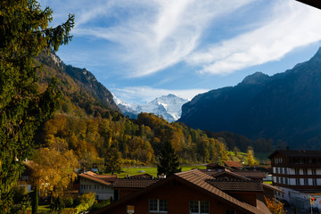 Wall Mural - Fabulous alpine wooden houses, green fields and famous touristic Grindelwald town with high North Face of Eiger mountains, Bernese Oberland, Switzerland, Europe