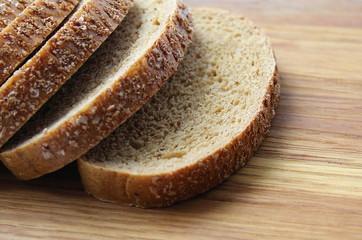 Fototapeta black bread sliced on slices lying on a cutting board obraz