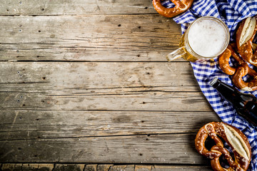 Oktoberfest food menu, bavarian pretzels with beer bottle mug on old rustic wooden background, copy space above Wall mural
