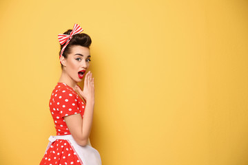 Portrait of funny young housewife on color background
