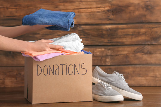 Female volunteer putting clothes into donation box on wooden background