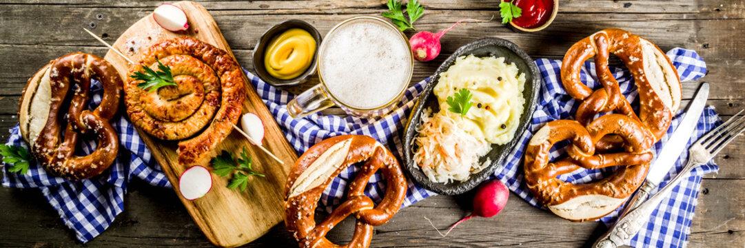 Oktoberfest food menu, bavarian sausages with pretzels, mashed potato, sauerkraut, beer bottle and mug old rustic wooden background, copy space above banner format