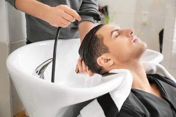 Hairdresser washing client's hair in beauty salon