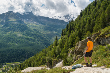 Hiking in the Italian Alps. Hiker with backpack, look at the panorama from above. The village below is Macugnaga and is located at the foot of Monte Rosa (on background), Anzasca valley, Italy
